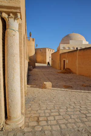 Impressive and colorful ramparts, located at the eastern side of Kairouan, Tunisia, with a cobbled pavement, a column and a dome
