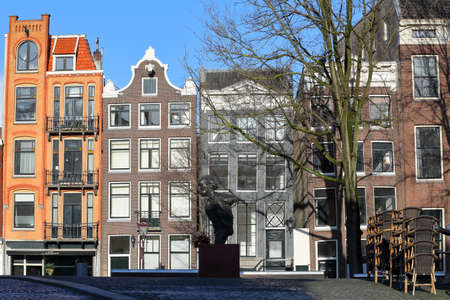 AMSTERDAM, NETHERLANDS - MARCH 03, 2020: Colorful heritage buildings with gable rooftops, located along Singel Canal, with the statue of Dutch writer Multatuli on the Torensluis bridge Standard-Bild - 144636253