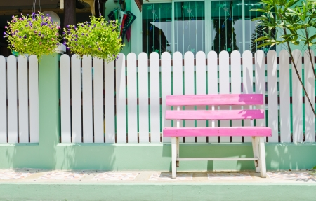pink wooden bench in front of white fence photo