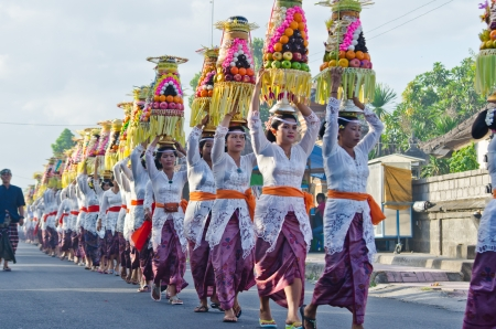 BALI - JUNE 25: Village women carry offerings of food baskets on their heads in a procession to the village temple June 25, 2012 in Bali, Indonesia. Editorial