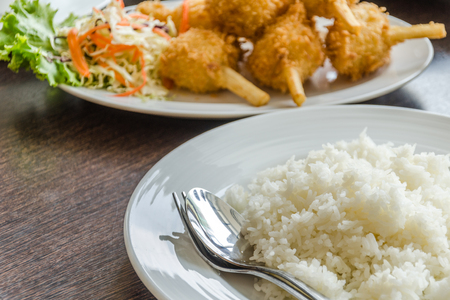 Fried shrimp ball on sugarcane skewers and plate of rice, Vietnamese food  photo