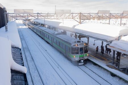 SHINSHINOTSU JANUARY 15: Train stop at railway station with snow of winter on January 15, 2016 in Shinshinotsu, Japan. Train is the important public transport rail network in Japan. Editorial