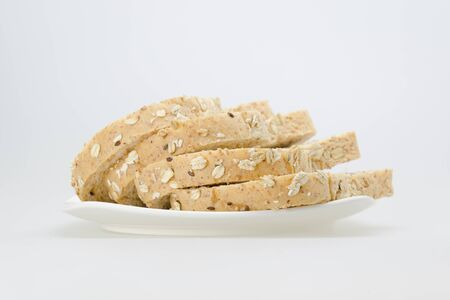 whole wheat with oat bread sliced on white plate. Banco de Imagens
