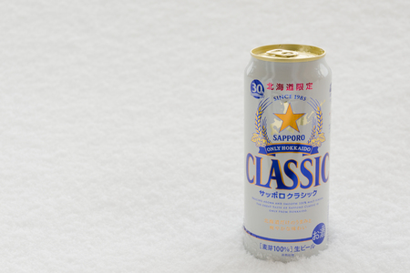 HOKKAIDO, JAPAN - JANUARY 14, 2016: A can of Sapporo Beer on snow. The Sapporo Beer is the oldest beer brand in Japan.
