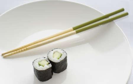 Two Kappa maki cucumber rolls sushi with green chopsticks on a white plate photo