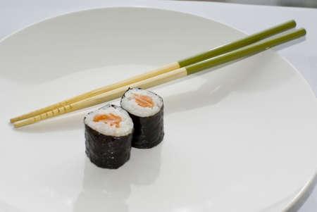 Two sake maki salmon rolls sushi with green chopsticks on a white plate photo