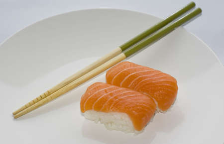 Two Sake nigiri salmon sushi with green chopsticks on a white plate photo