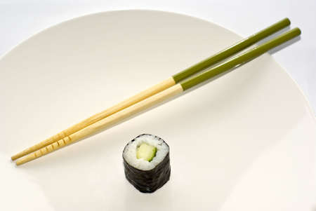 One Kappa maki cucumber roll sushi with green chopsticks on a white plate