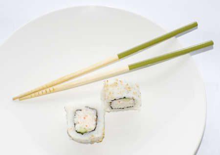 Two California maki sushi rolls with green chopsticks ona white plate photo
