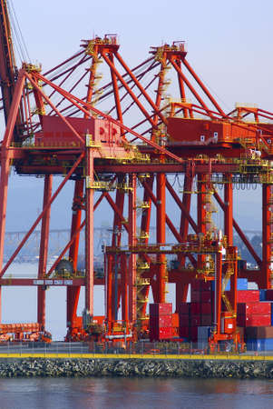 Cranes in red at an industrial port with a bridge in the back photo