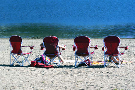 relaxion: People relaxing and sunbathing in a row of beach chairs on the sand in front of the ocean on a sunny summer day