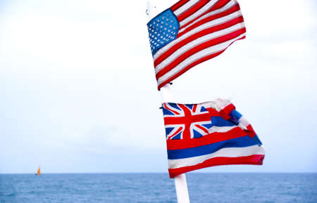 Flag of United States of America and State of Hawaii flying on a ship mast on the open Pacific Ocean