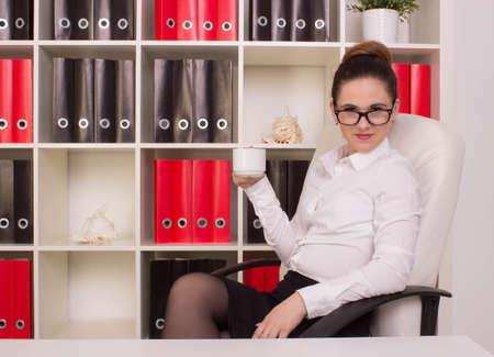 mujeres morenas: Mujer de negocios sentado con la taza de café Foto de archivo