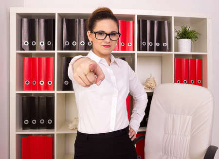 pretty brunette woman: Business woman pointing in office
