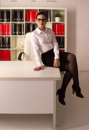 mujeres morenas: Mujer de negocios sentado en el escritorio