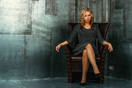 belle femme en robe noire sur une chaise en cuir Banque d'images