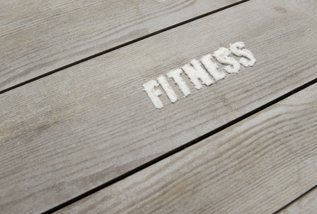 fits in: Fitness written on wood with whey powder