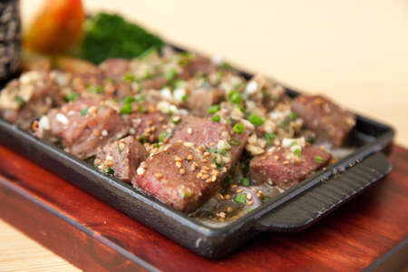 The View of Delicious Japanese Food Sizzing Beef Granules on the Table. Stock Photo