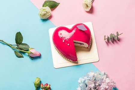 Heart-shape Mousse Cake on Red and Blue Background with Beautiful Hydrangea. Stock Photo