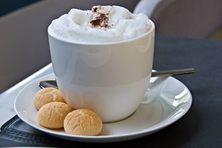Hot cappuccino or latte coffee with frothed milk and cookies photo