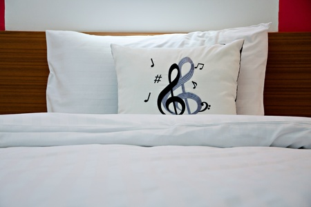 Pillows with music notes on the linen bed photo