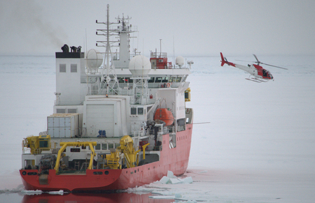 Icebreaker ship and helicopter in the sea of Antarctic photo