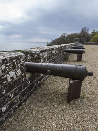 a row of canons lined up at sea defense