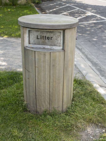 a wooden litter bin in a large park Stock Photo
