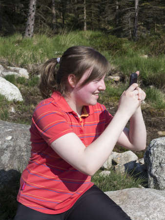 young girl taking a picture or texting with her phone whilst hiking in the mountains Stock Photo