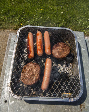 a mixture of sausages and burgers cookin on a bbq Stock Photo