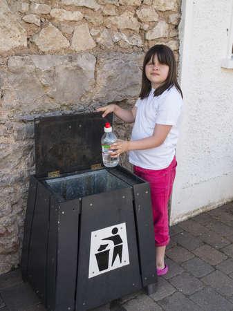 ni�os reciclando: Chica joven que pone la basura en un contenedor