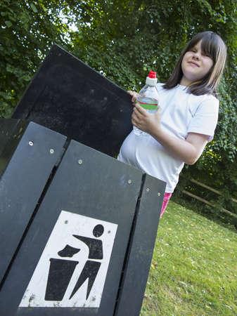 young girl throwing trash in a bin