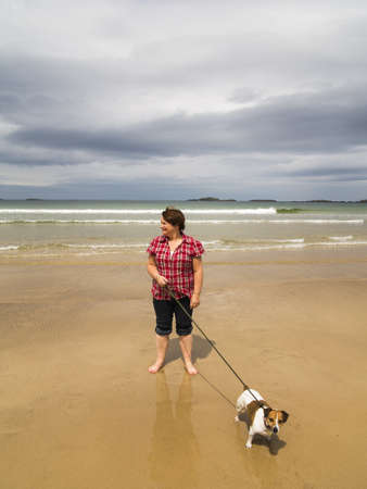 woman walking dog along beach of portrush east strand she has a jack russell terrier Stock Photo