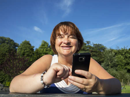 mature woman laughing using a mobile phone outdoors