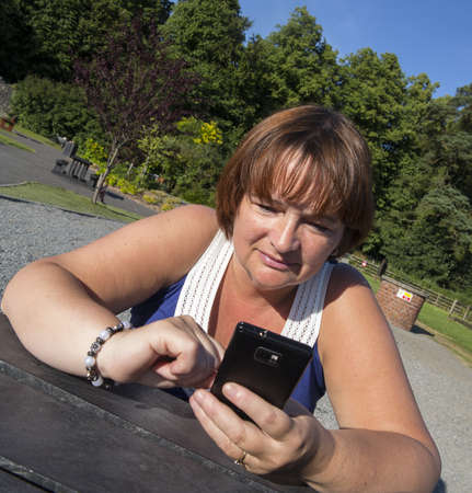 mature woman in park texting on mobile phone Stock Photo