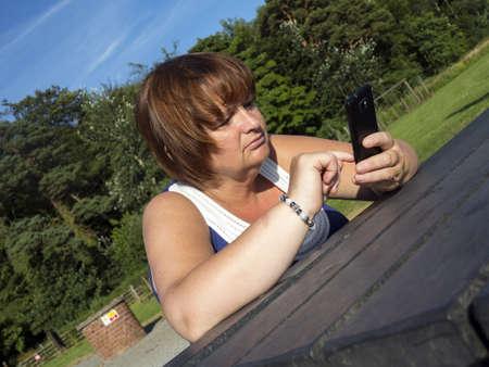 mature woman texting at an outdoor park bench