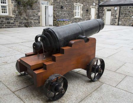 small cannon sitting in a large courtyard
