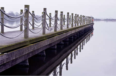 wooden jetty on a desolate lake with a reflection on the water Stock Photo