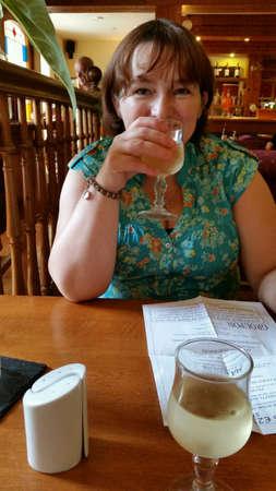 Woman drinking at hotel bar Stock Photo