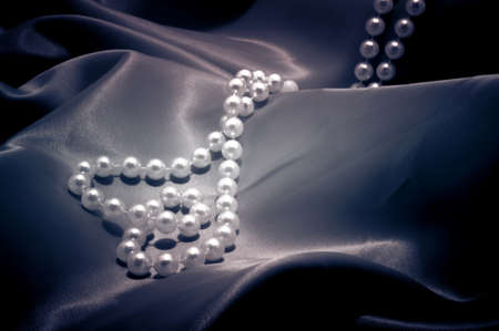 Pearls necklace in the shape of heart on he satin photo