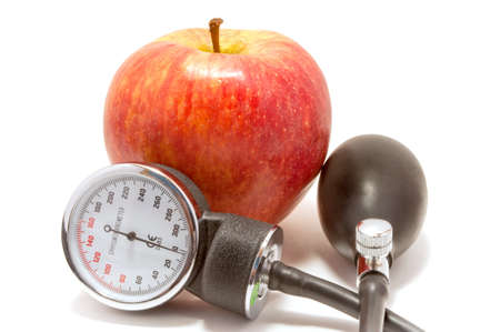 Red apple and sphygmomanometer, isolated on white photo