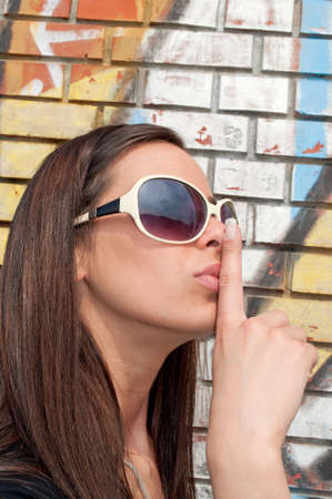 Girl shows shhh next to a wall with graffiti Stock Photo - 9211271