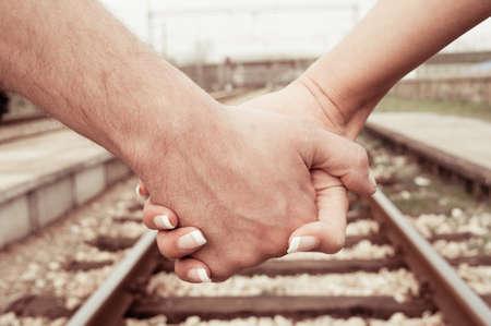 Couple walk, hand by hand, along railroad photo