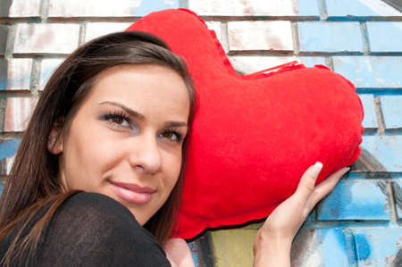 Girl with heart-shape pillow next to a wall with graffiti Stock Photo - 9211264