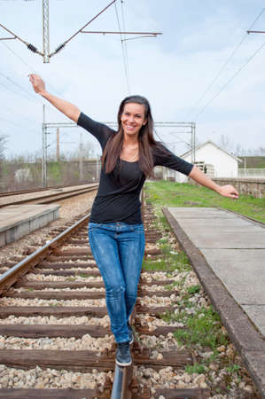 Young brunette girl walking on the rail photo