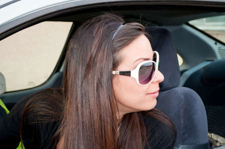 Brunette girl looking through car window Stock Photo - 9239983