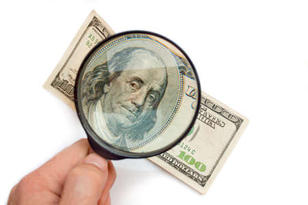 an investigation: Hand holding magnifier glass above hundred-dollars bill, isolated on white
