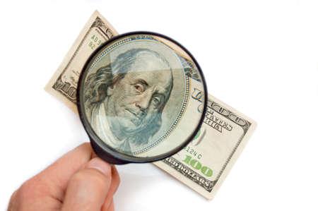 vals geld: Hand met Vergrootglas glas boven de honderd dollar bill, geïsoleerd op wit Stockfoto