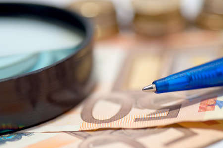 50 euro: Pen and magnifier glass on the 50 Euro banknotes and blurred coins in the background Stock Photo