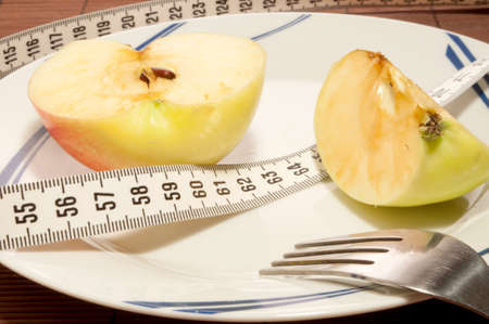 Sliced apple, centimeter tape and fork on the plate photo